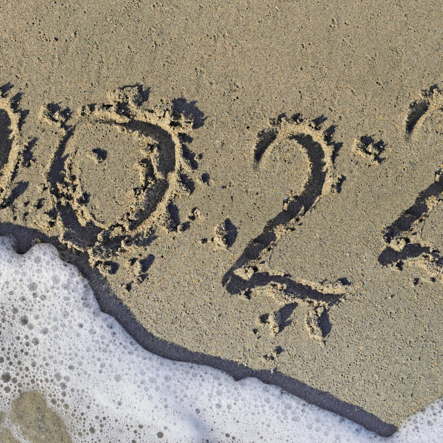"""""""2022 written in the sand of a beach on the edge of the foam of w"""" stock image"""