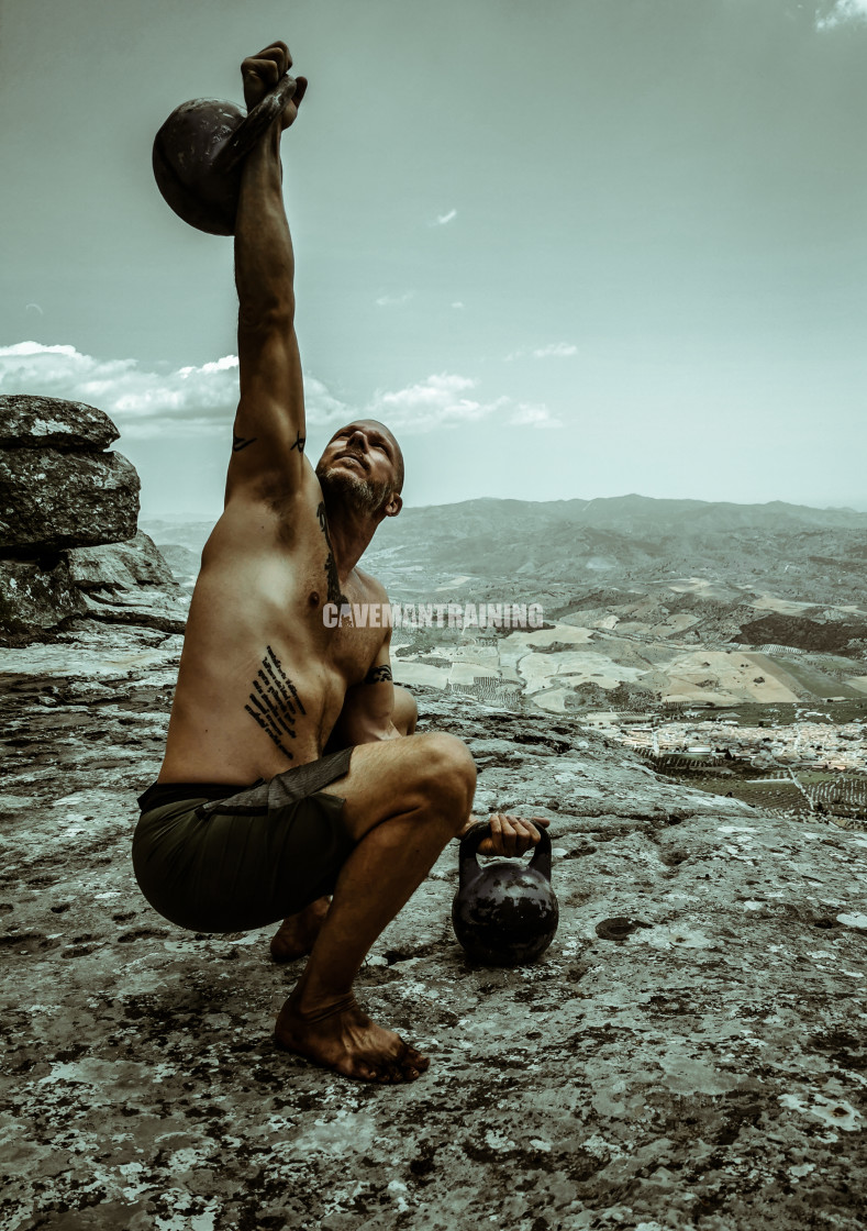 """A Man Lifts a Kettlebell Overhead From Squat"" stock image"