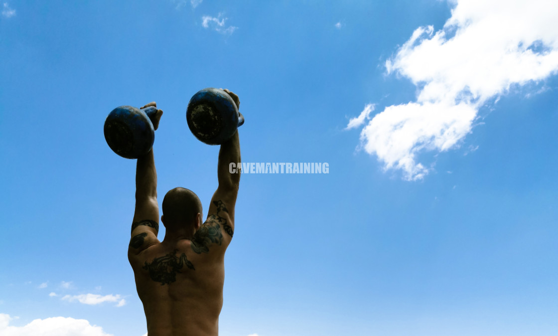 """A Fit Man Presses Two Kettlebells Overhead"" stock image"
