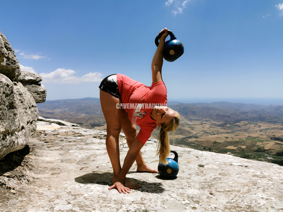 """A Woman Performs The Kettlebell Windmill"" stock image"