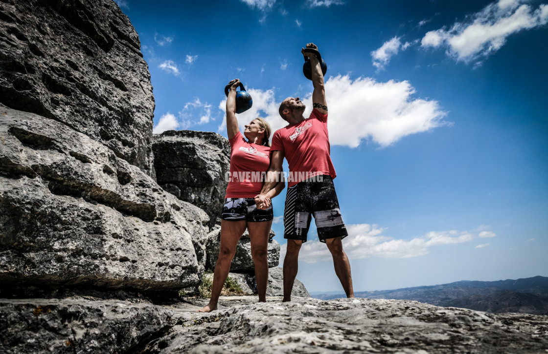 """A Couple On A Mountain Holding Hands And Kettlebells"" stock image"