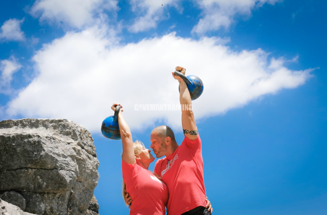 """A Couple Kissing With A Kettlebell Overhead"" stock image"