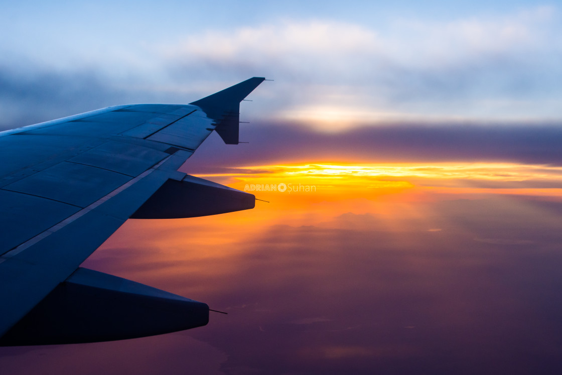 """""""Wing of the plane at sunset in flight"""" stock image"""