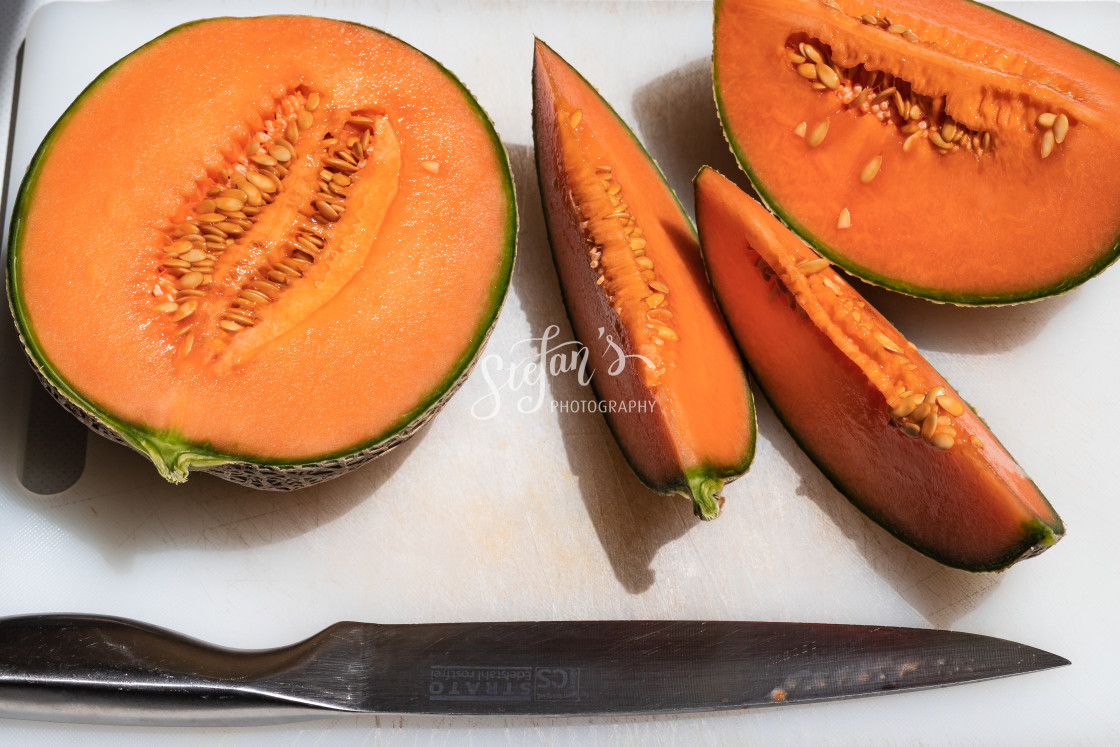 """""""Melon sliced on a white cutting board"""" stock image"""