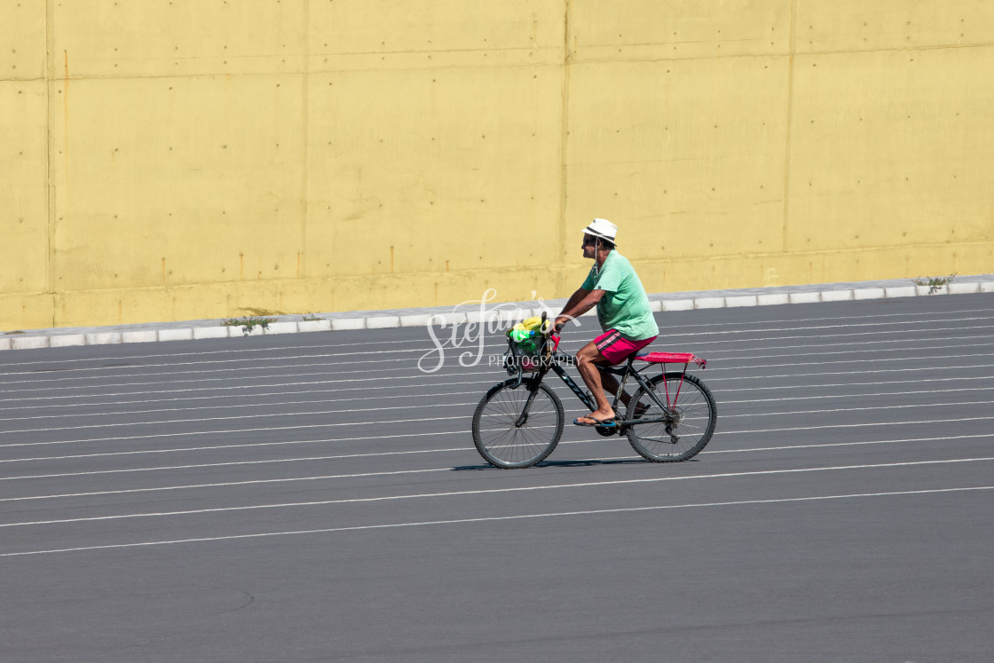 """""""Man on bicycle in front of concrete wall in yellow"""" stock image"""