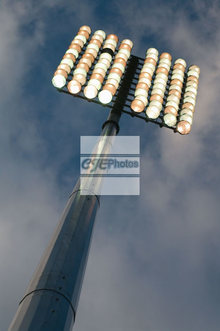 """Floodlight, switched on, against a blue sky."" stock image"