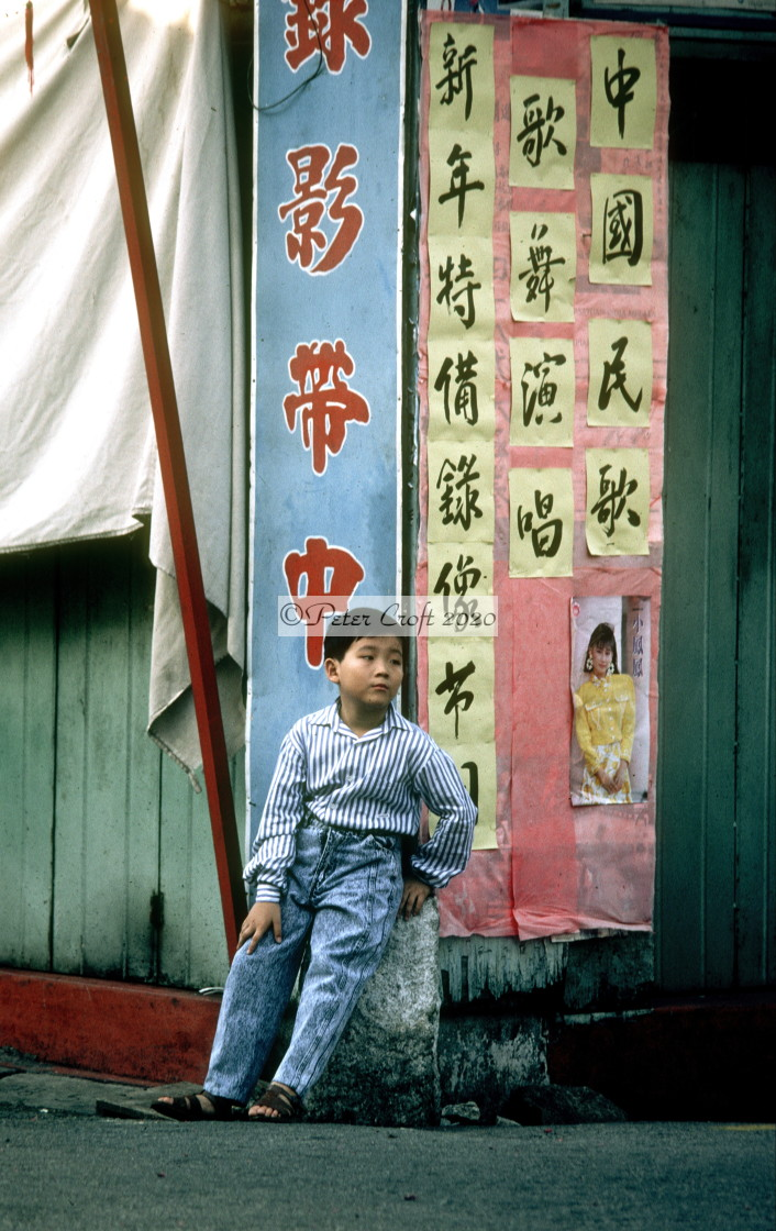 """A boy with Chinese signs, Malacca, Malaysia."" stock image"
