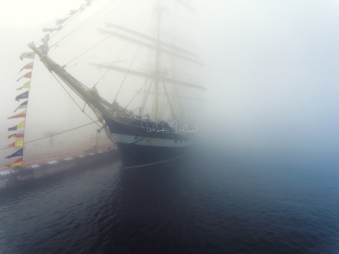 """Ship with flags in the fog early morning"" stock image"
