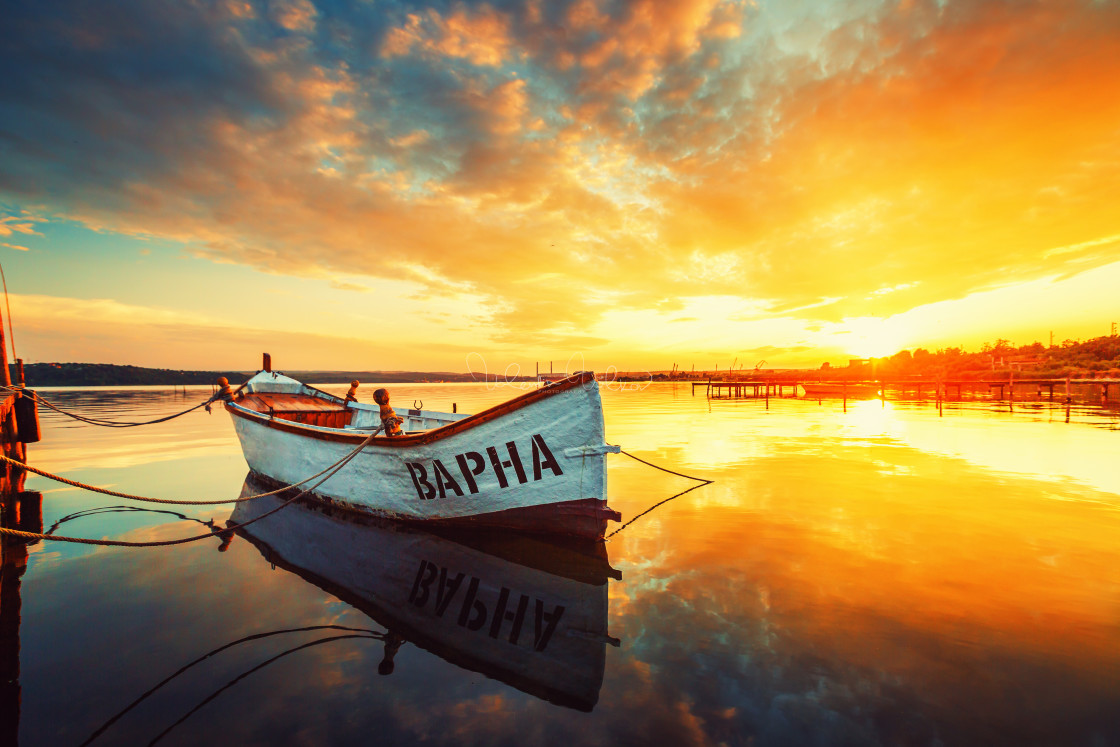 """Fishing Boat on Varna lake with a reflection in the water at sun"" stock image"