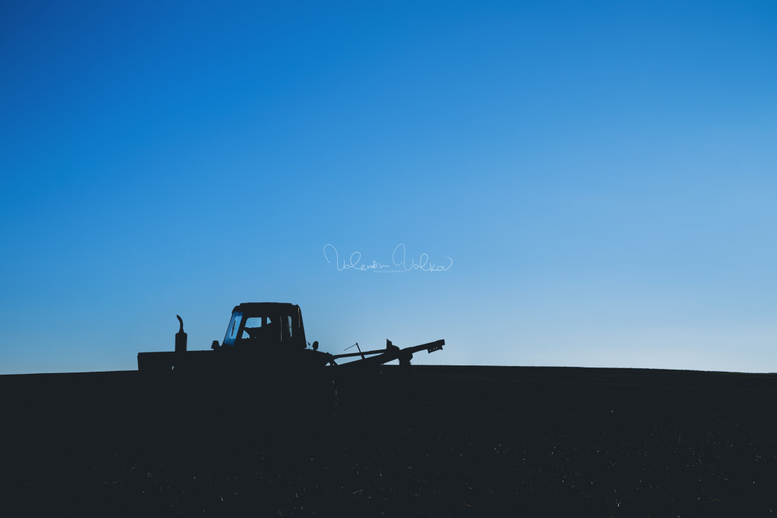 """Tractor on the field. Silhouette against a blue sky"" stock image"