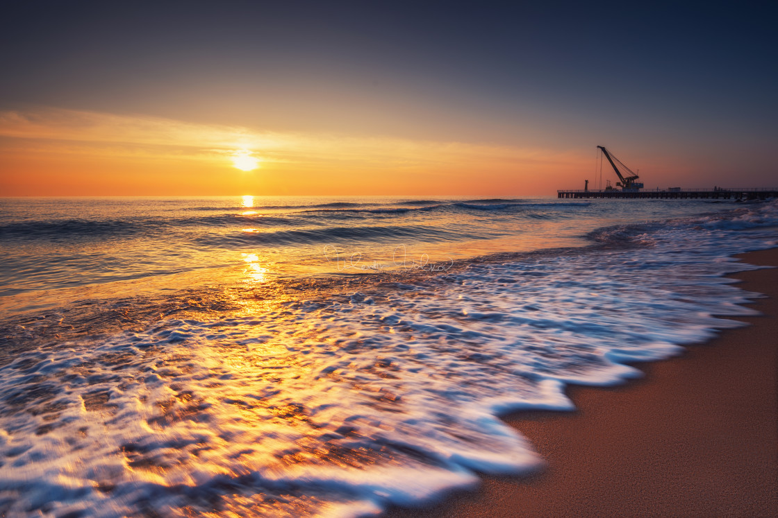 """""""Sunrise on the sea and beach. Waves washing the sand. Industrial"""" stock image"""