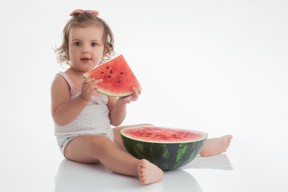 """Baby girl eating watermelon slice isolated on white background"" stock image"