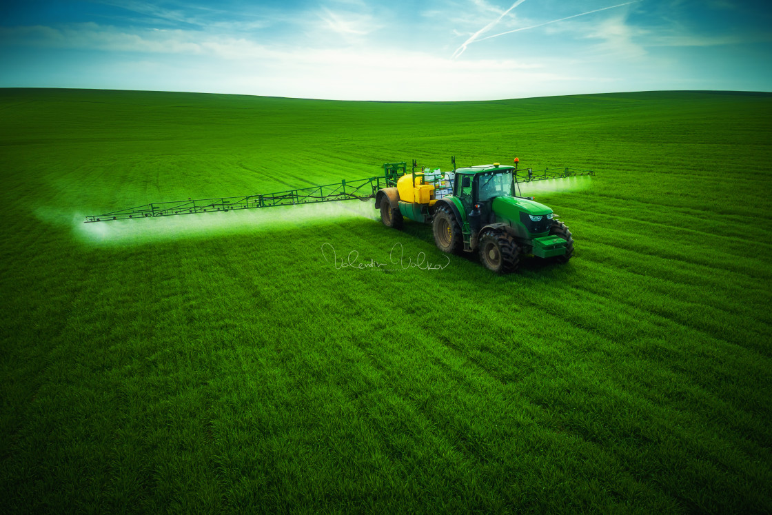 """""""Aerial view of farming tractor plowing and spraying on field"""" stock image"""