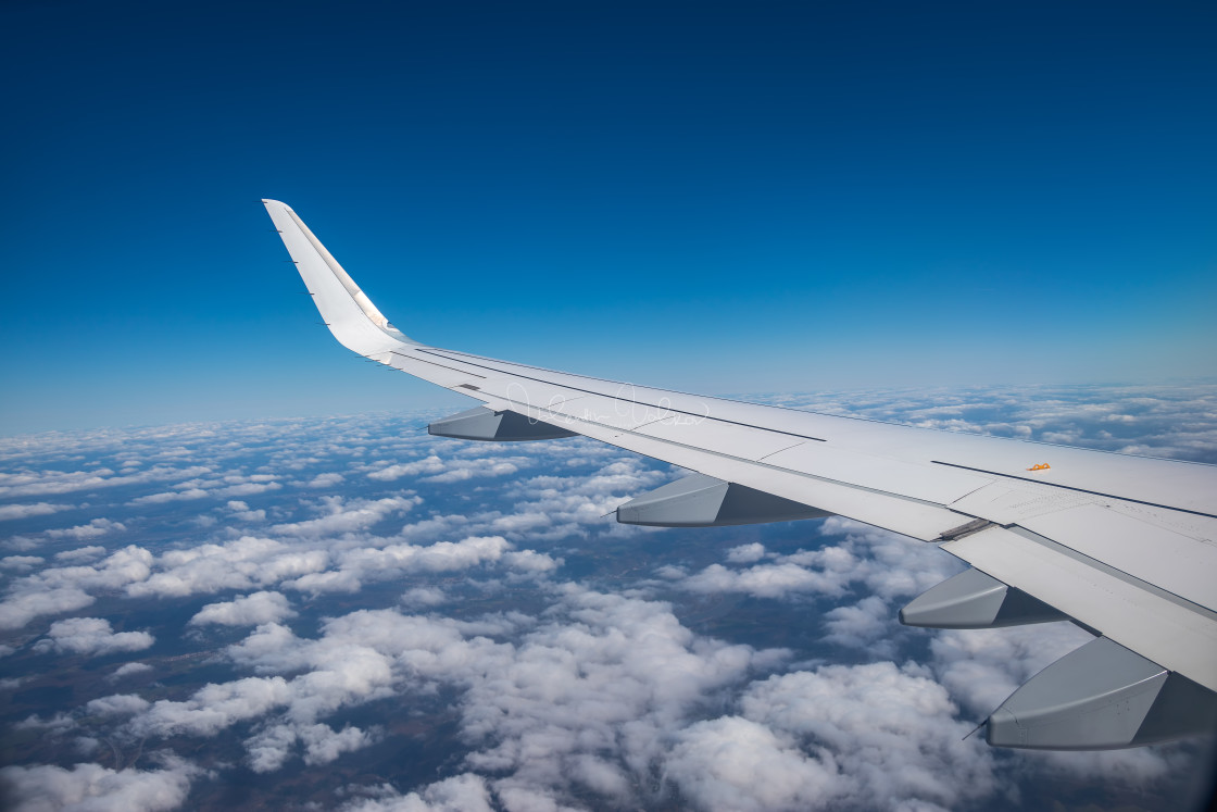 """Aerial view from the plane over fluffy clouds"" stock image"