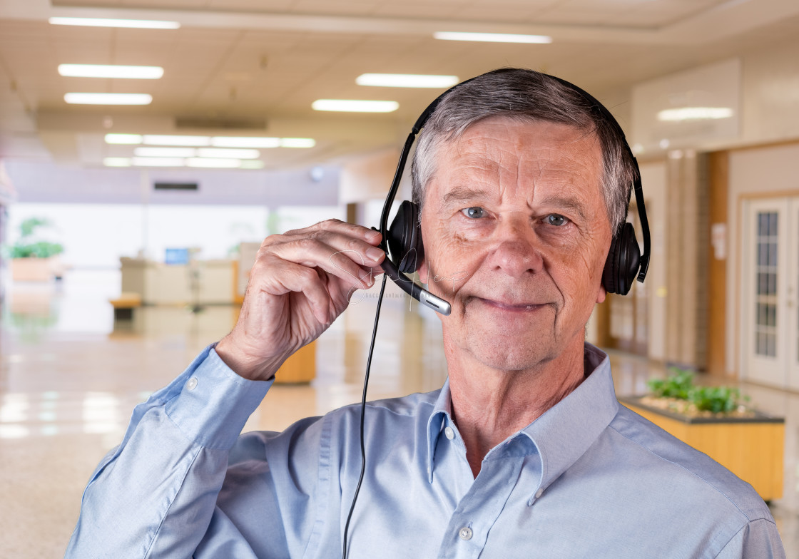 """""""Senior man using headset to communicate with team or customers"""" stock image"""