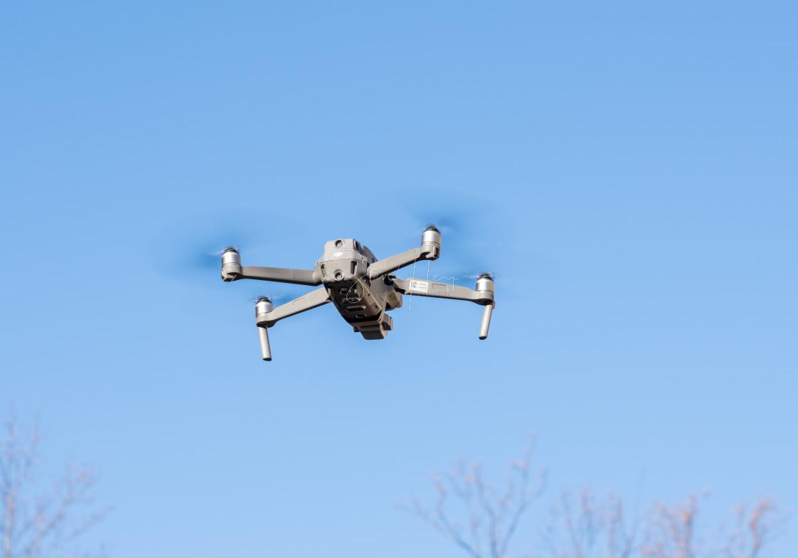 """DJI Mavic Pro 2 drone flying above the camera against blue sky"" stock image"