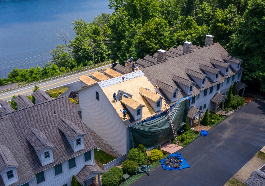 """""""Drone view of roofing contractor removing shingles from a roof ready for..."""" stock image"""