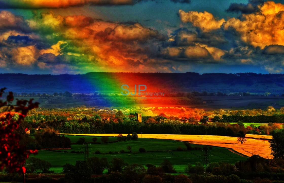 """A Church lit by a Rainbow"" stock image"