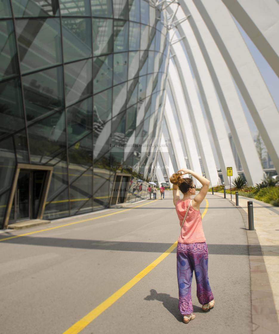 """Woman walking outside Flower Dome, Singapore"" stock image"