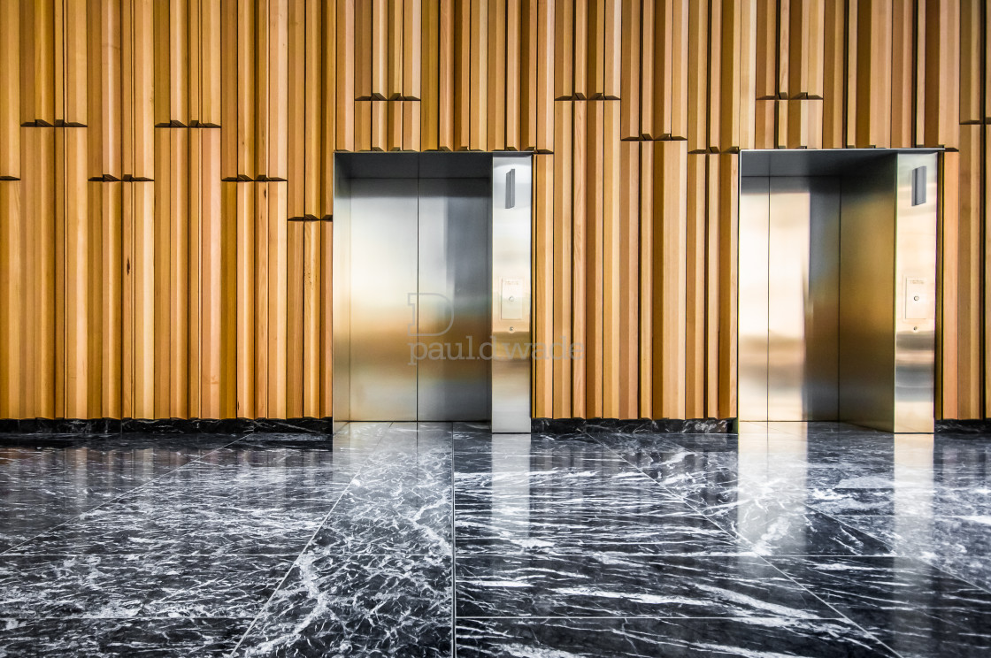 """""""A modern lift lobby with black and white marble floor and modern wood wall panelling"""" stock image"""