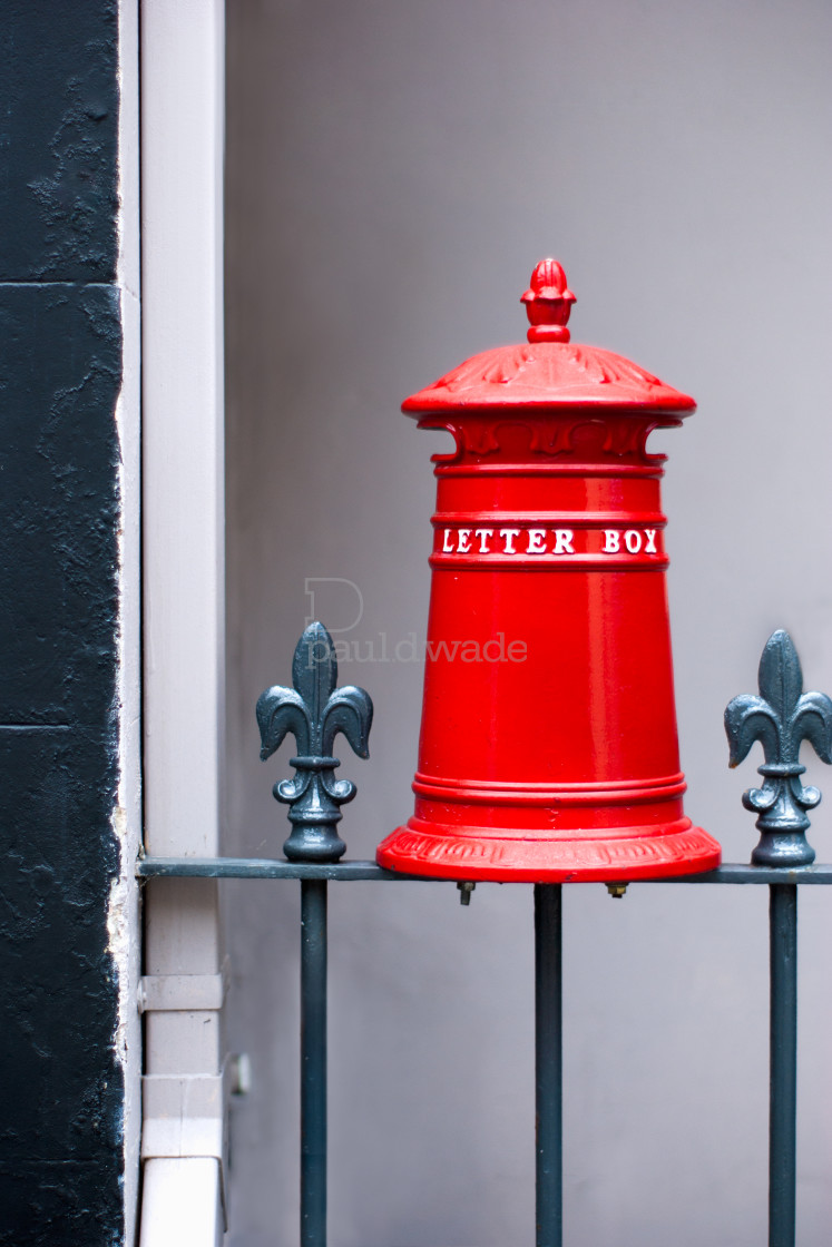 """""""Mini bright red UK style post box on a fence outside a home"""" stock image"""