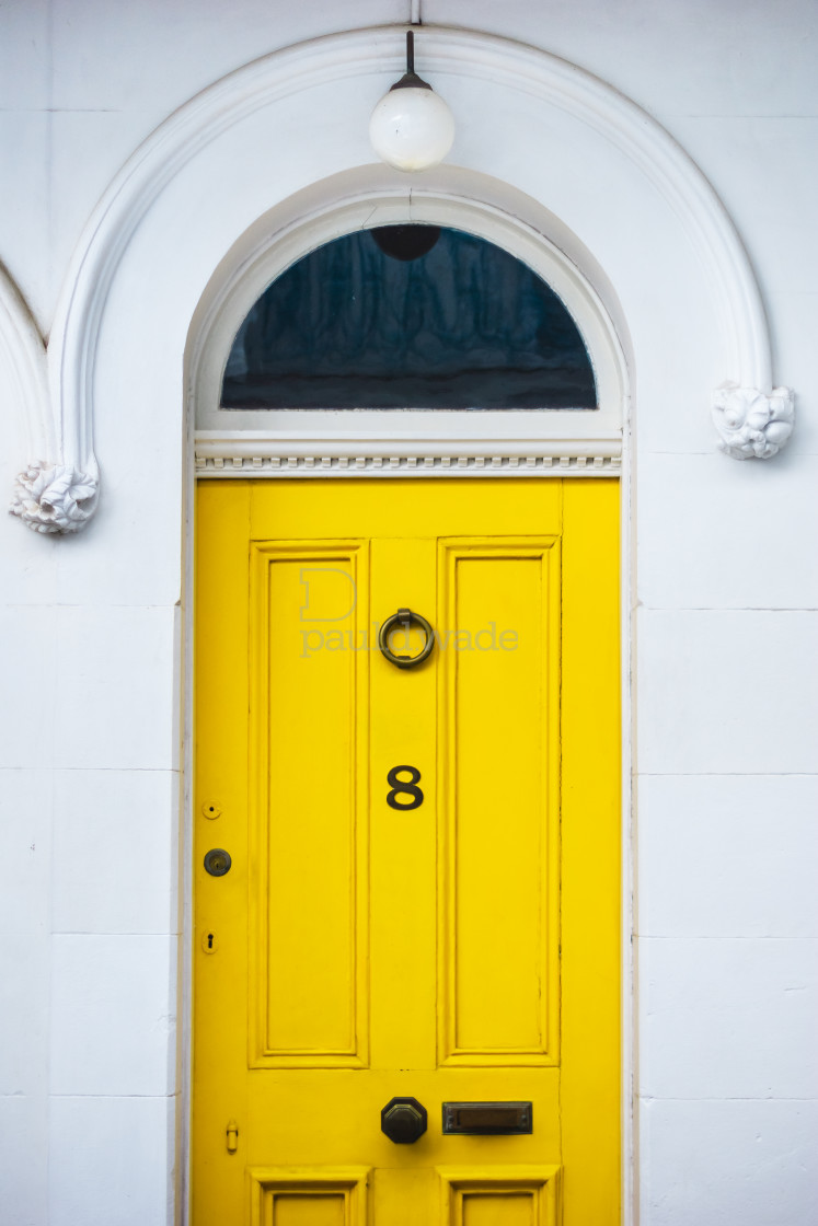"""""""Bright yellow front door with decorative panels and mouldings"""" stock image"""