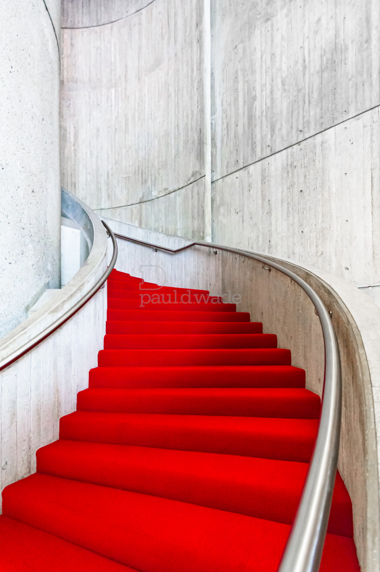 """""""A bright red carpet winds its way up a curved staircase"""" stock image"""