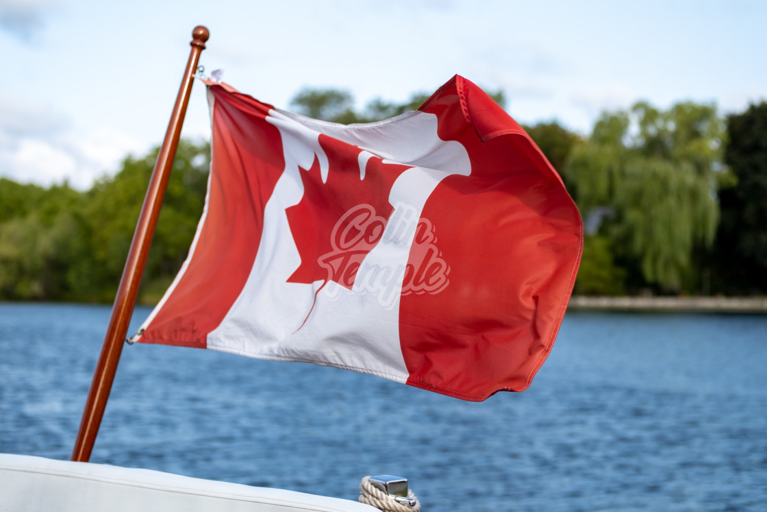 """Canadian flag flies on boat's stern"" stock image"