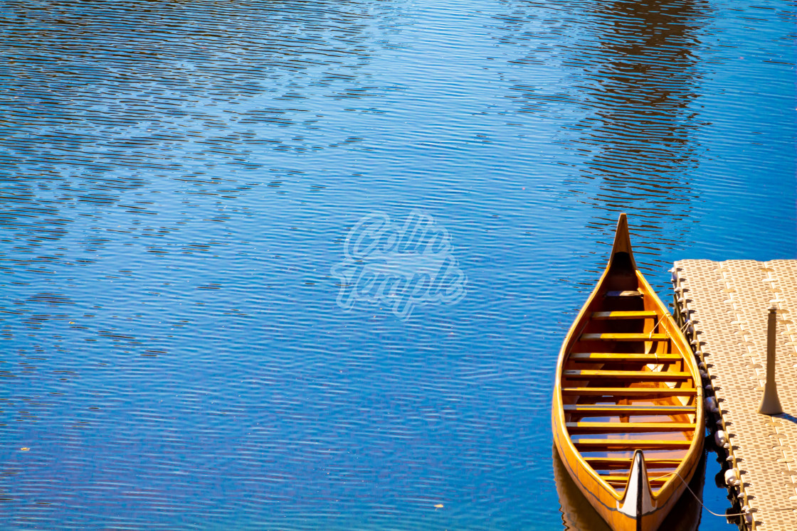 """""""A Wooden Canoe Docked in a River"""" stock image"""