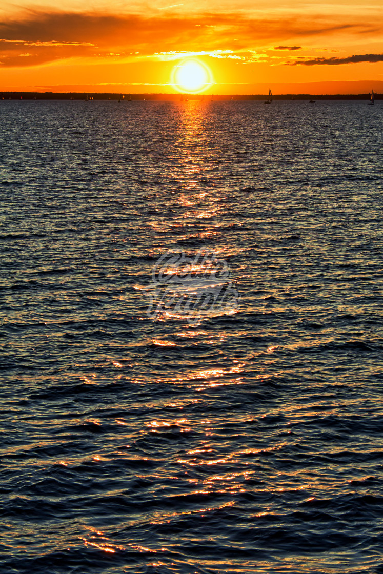 """Distant sailboats and sunset over dramatic water; Ottawa, Ontario, Canada"" stock image"
