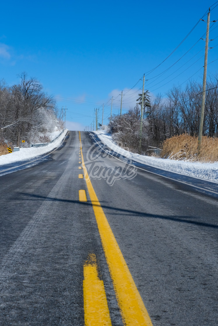 """""""Empty road up hill in winter"""" stock image"""