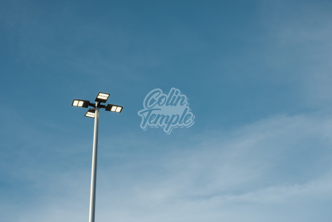"""Elevated street lights on a pole against sky"" stock image"