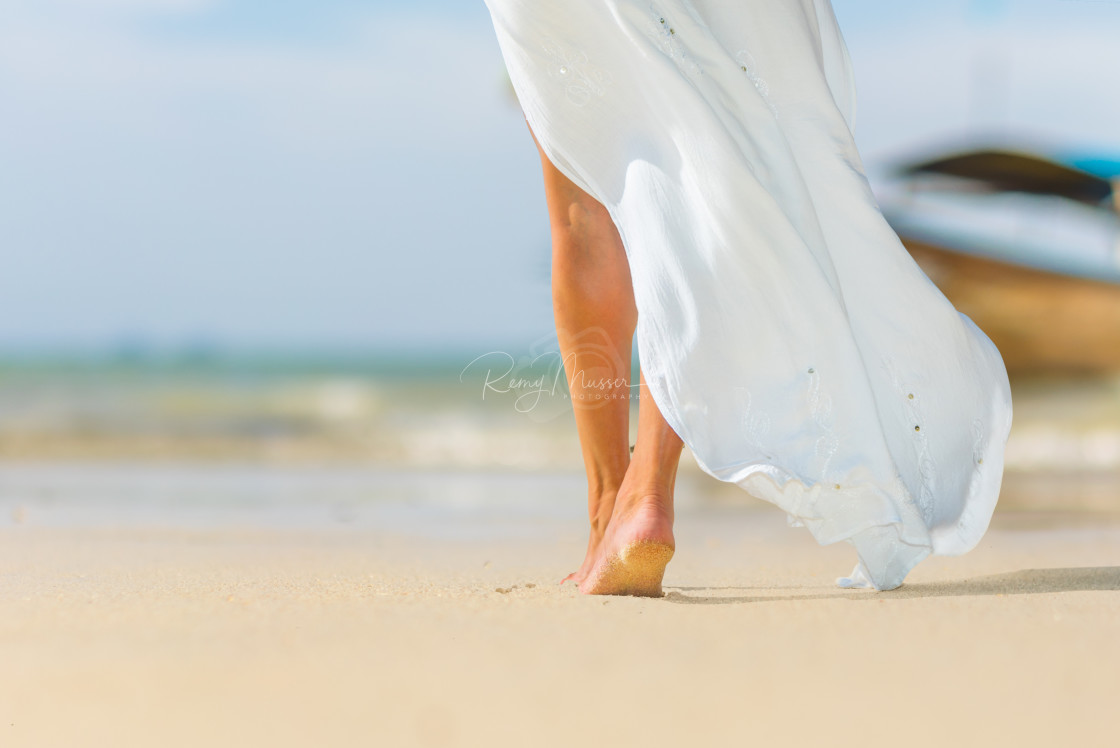 """White pareo woman legs walking on tropical beach vacation. Close"" stock image"