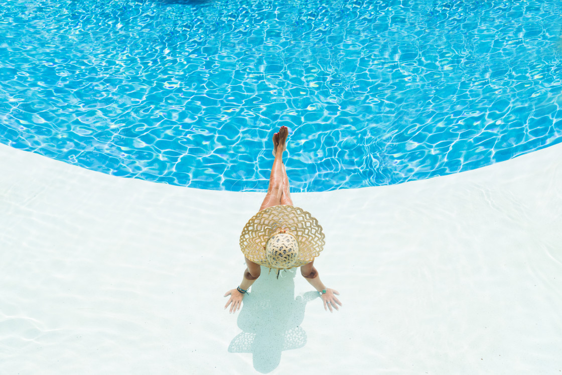 """beautiful woman in a hat sitting on the edge of the pool"" stock image"