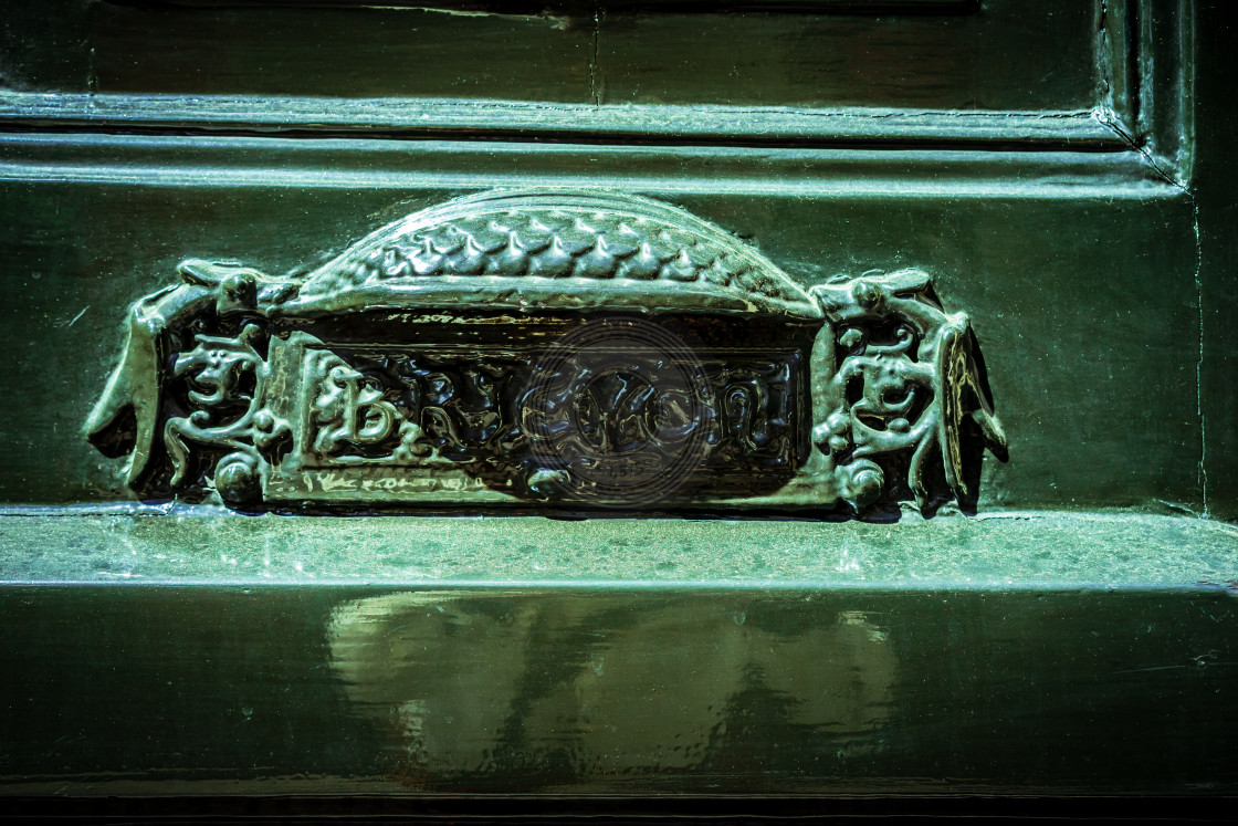 """Ornate letterbox in a green door"" stock image"