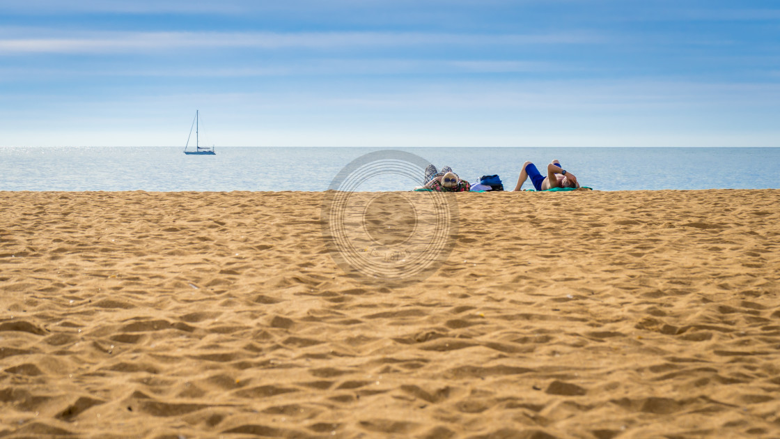 """Couple lying on an empty beach"" stock image"