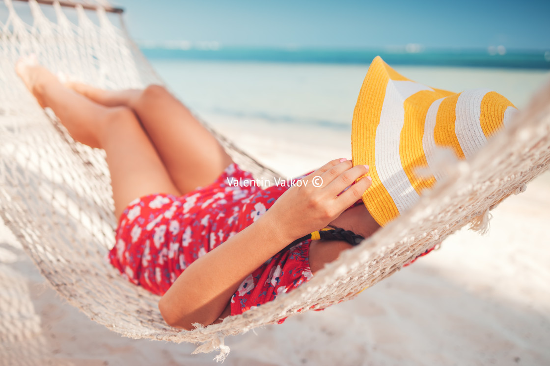 """""""Young girl resting in a hammock under tall palm trees, tropical"""" stock image"""