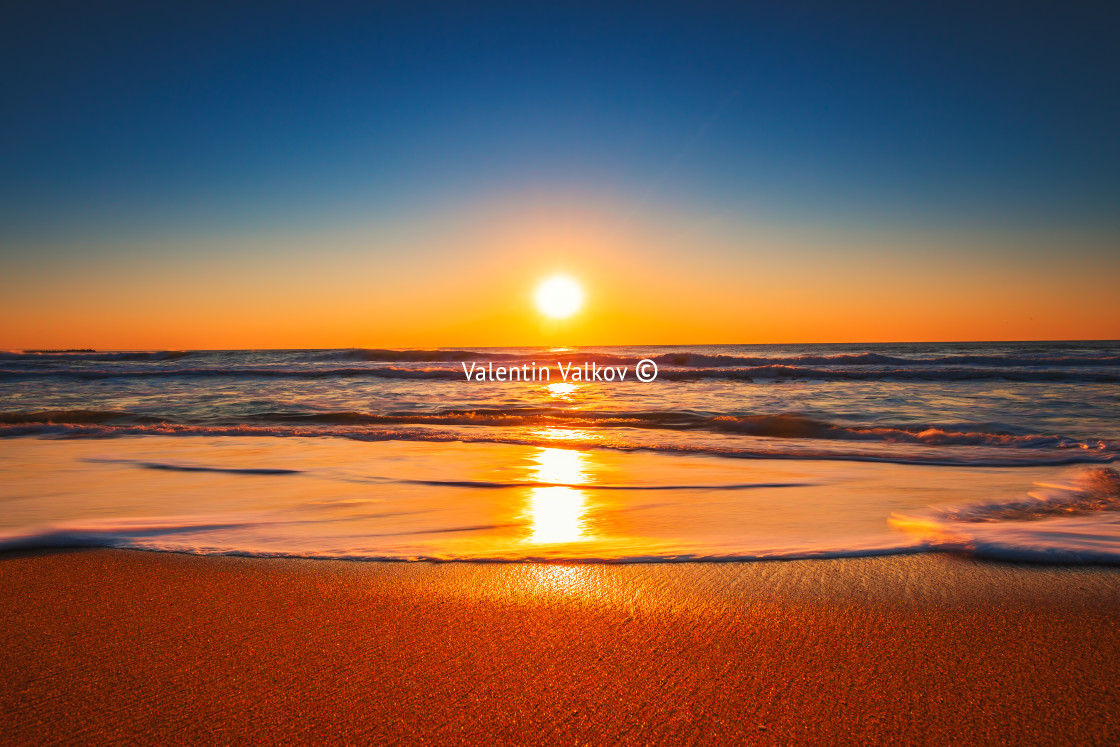 """""""Beach sunrise or sunset with clear blue sky and rising sun"""" stock image"""
