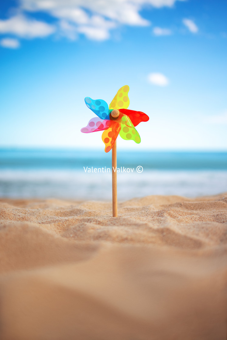 """Pinwheel on a beach sand against blue sky and sea, summer vacati"" stock image"