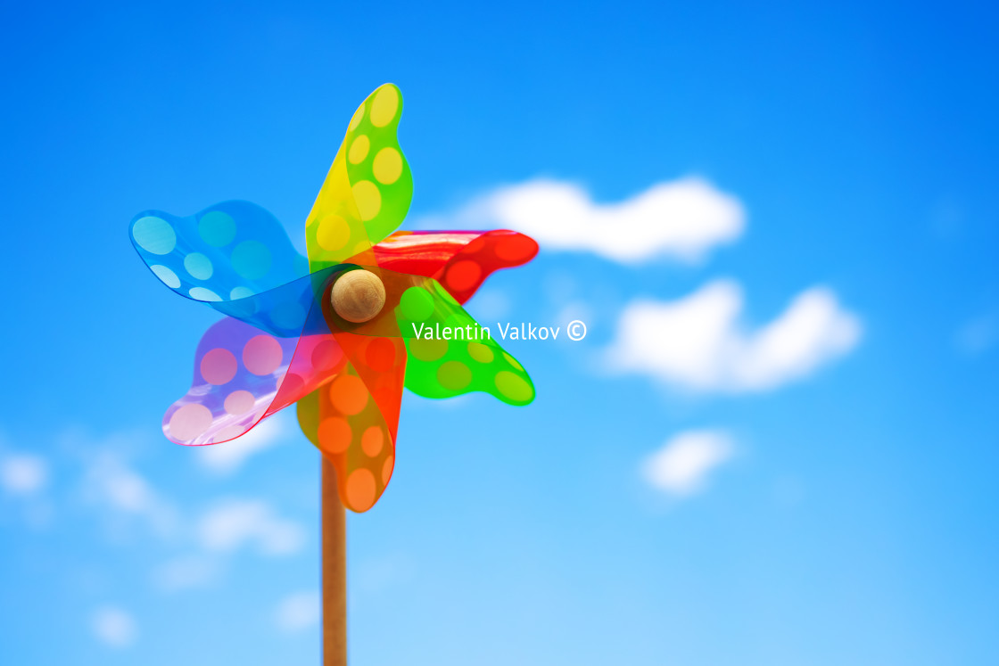 """""""Pinwheel on blue sky with clouds. Colorful wheel kids toy"""" stock image"""
