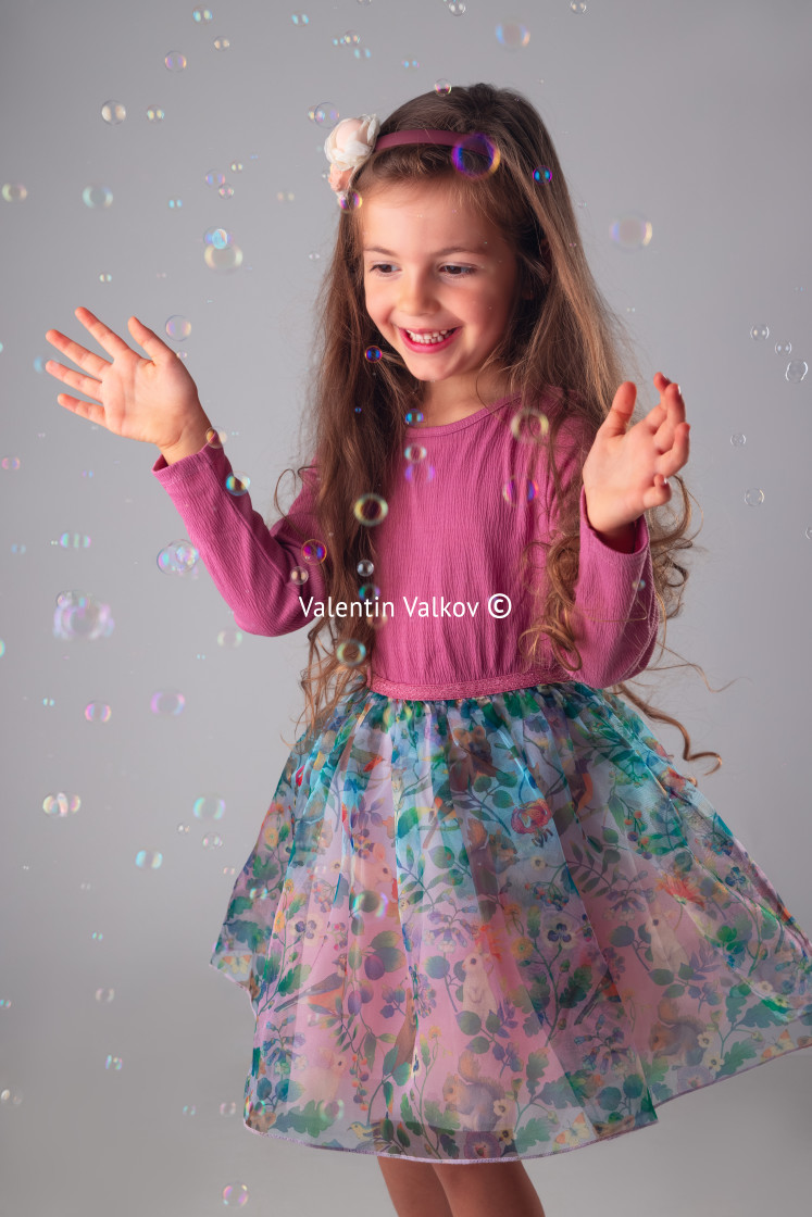 """""""Happy little girl in party dress playing with soap bubbles portr"""" stock image"""