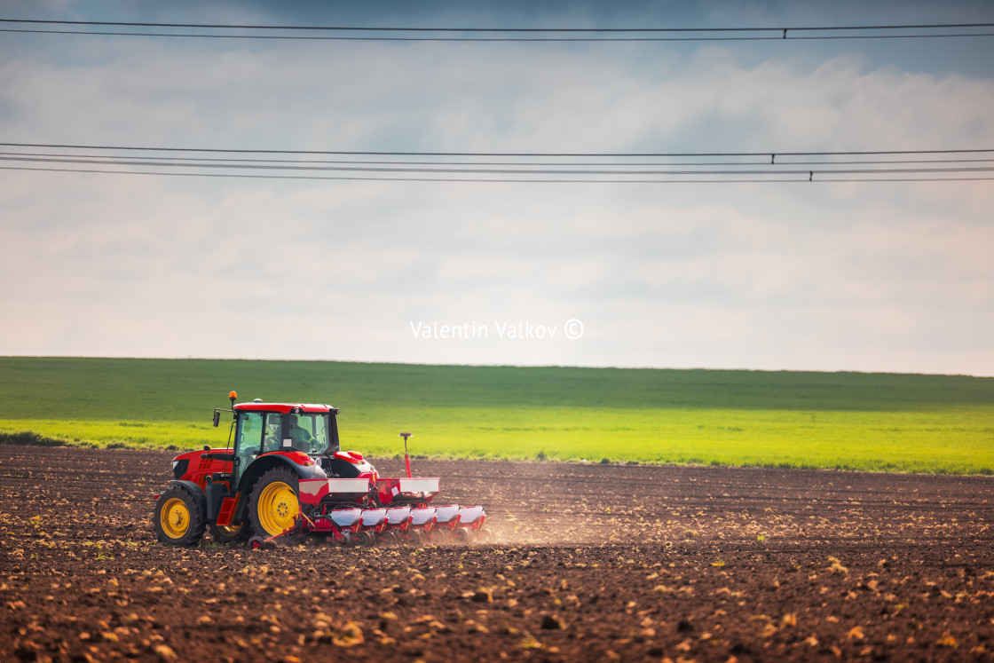 """""""Farmer with tractor seeding crops at field"""" stock image"""