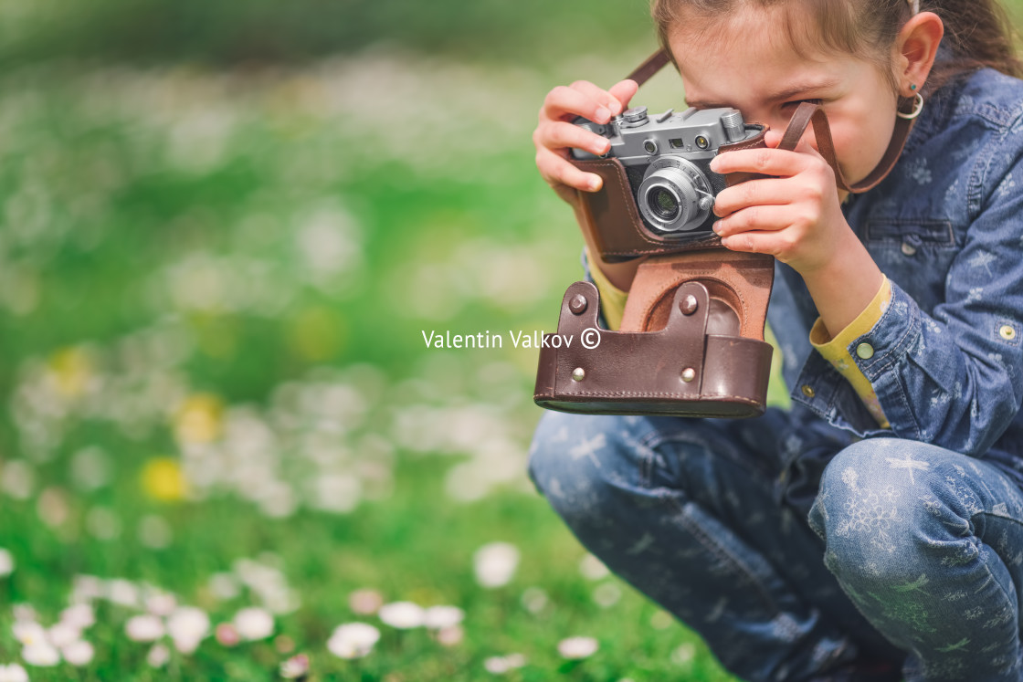 """""""Little girl with old vintage camera making photos of surrounding"""" stock image"""
