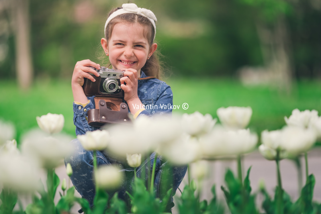 """""""Little girl with old vintage camera making photos of tulips in f"""" stock image"""