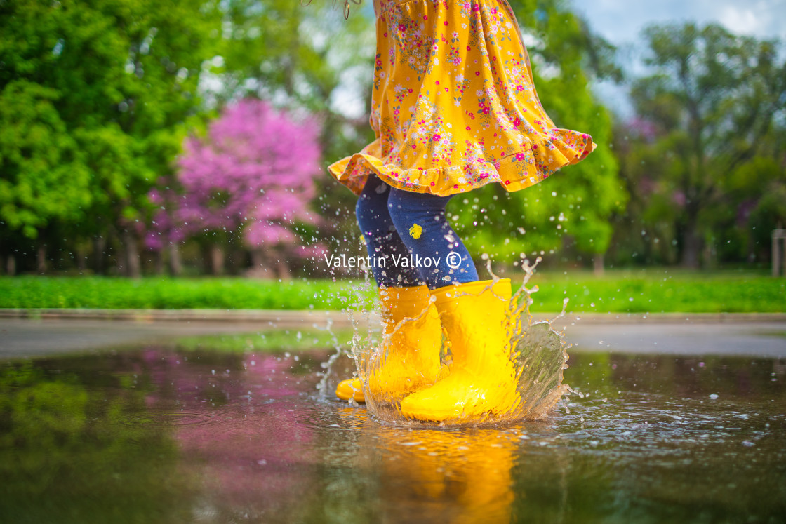 """""""Happy child girl with yellow rubber boots jumping in puddle at"""" stock image"""