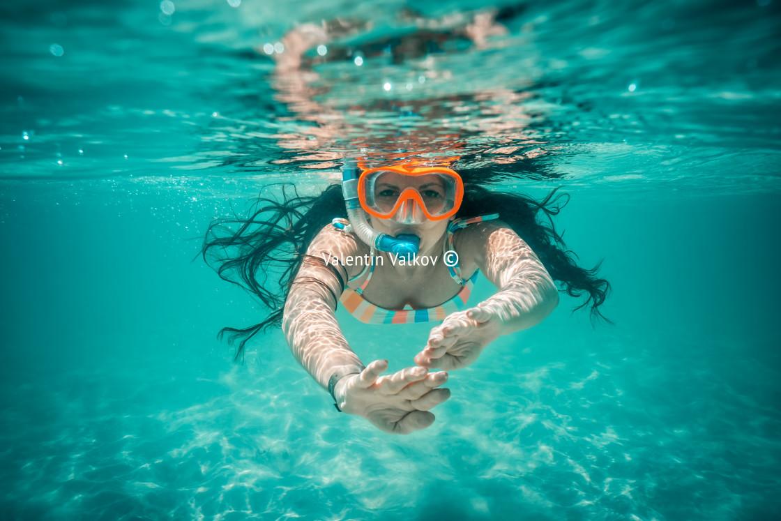 """Underwater view of beautiful woman swimming in blue ocean water"" stock image"
