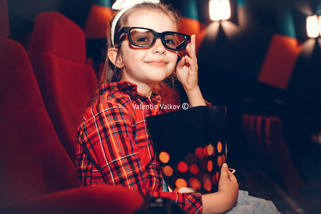 """""""Little girl watching cartoon 3D movie in cinema and eating popco"""" stock image"""