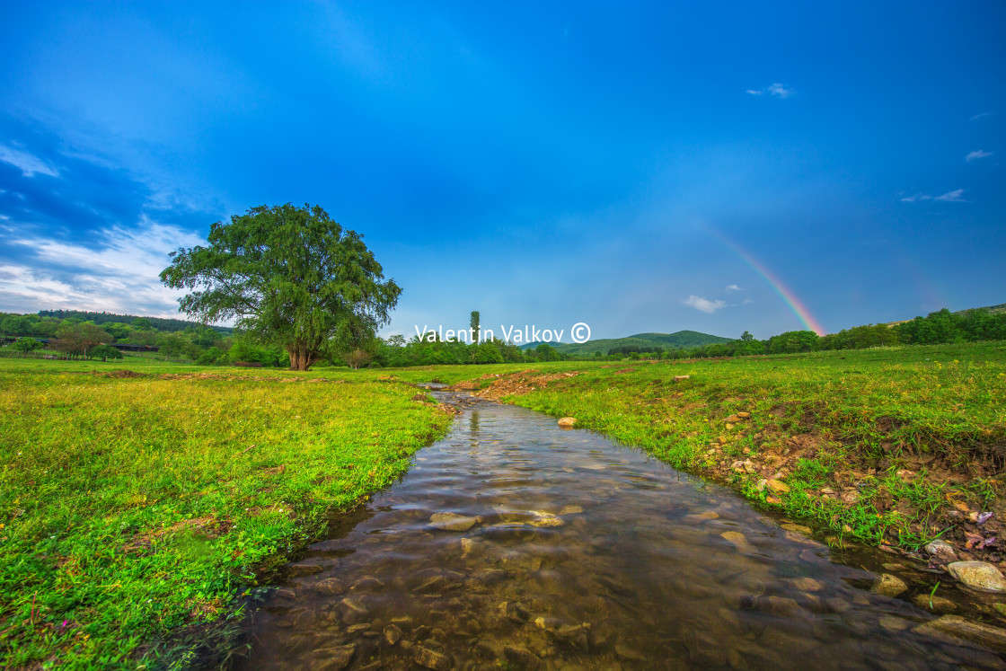 """""""Rainbow over fields and trees and river"""" stock image"""