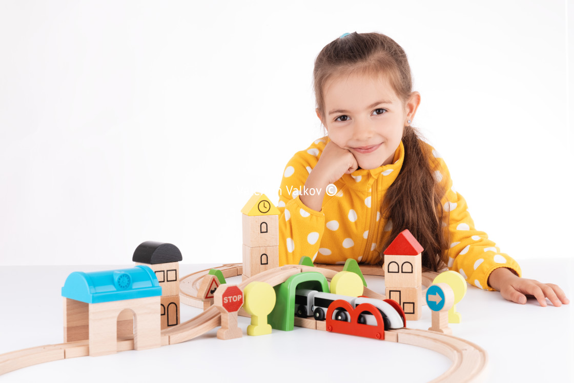 """""""Cute kid, little girl playing with wooden toys train and railway"""" stock image"""
