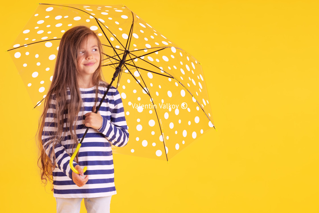 """""""Happy emotional girl laughing with umbrella on colored yellow ba"""" stock image"""